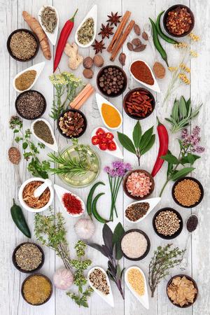 Large herb food seasoning sampler over distressed white wood background.