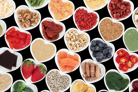 comida rica: Súper alimentos vegetales y fruta selección para una buena salud en forma de corazón platos de porcelana sobre fondo negro, con alto contenido de vitaminas y antioxidantes. Foto de archivo