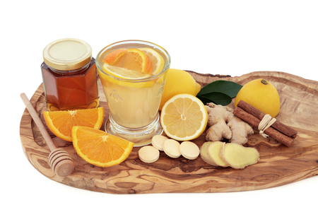 cold cure: Cold and flu healing drink with vitamin c tablets, orange, lemon, ginger and cinnamon spice on olive wood board over white background.