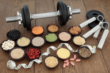 super food: Body building equipment with dumbbells and hand grippers with health and super food  including supplement powders, ginseng vitamin pills, pulses, seeds, nuts, grains and tape measure. Stock Photo