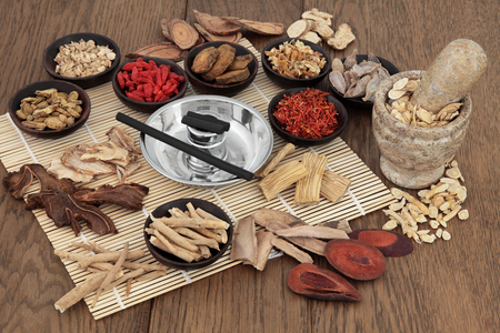 yin: Moxa sticks and chinese herbs used in traditional herbal medicine with mortar and pestle over bamboo and oak background.