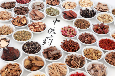 Traditional chinese medicinal herb ingredients with calligraphy on rice paper. Translation reads as chinese herbal medicine. Stockfoto