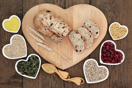 carbohydrates: Cranberry and seed bread loaf on a heart shaped wooden board with wheat sheaths, lovespoon with grain, pumpkin and sunflower seeds, cranberries, oatmeal and olive oil on old oak background. Stock Photo