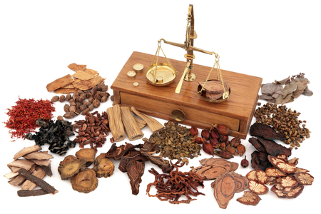 Chinese herb ingredients used in traditional herbal medicine with old brass scales over white background.