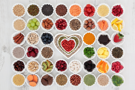 Large superfood selection in porcelain crinkle bowls and heart shaped dishes over distressed wooden background. High in vitamins and antioxidants.