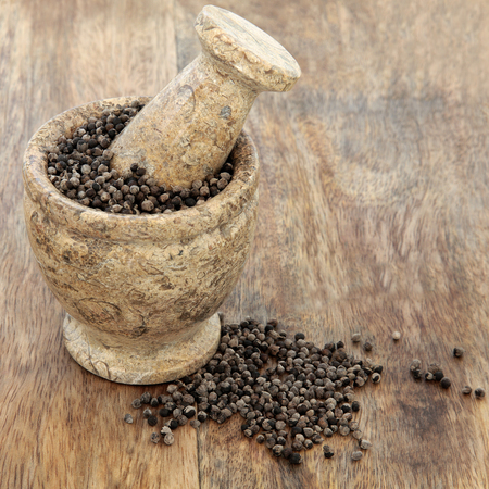 aphrodisiac: Vitex agnus castus herb used in natural alternative herbal medicine in a mortar with pestle over old wood background. Used as an aphrodisiac and tonic for male female reproductive systems.
