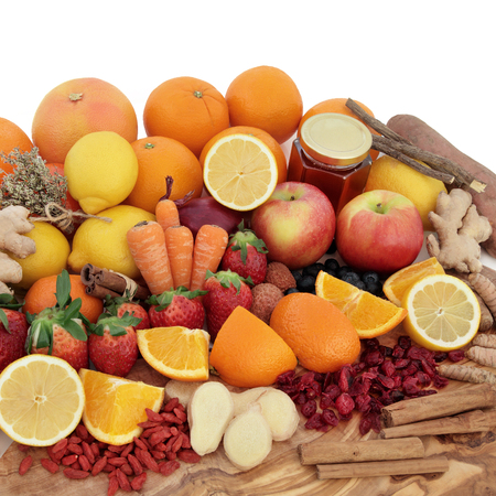 cold remedy: Large antioxidant food selection for cold remedy with foods on an olive wood board over white background.