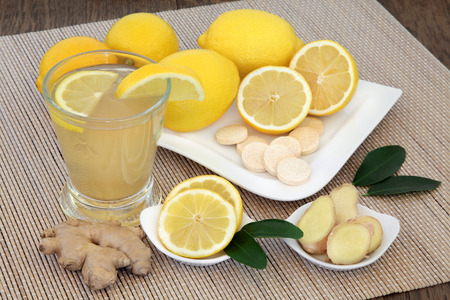 cold cure: Antioxidant natural cold remedy relief drink with lemon fruit, vitamin c tablets and ginger spice on bamboo over oak background.