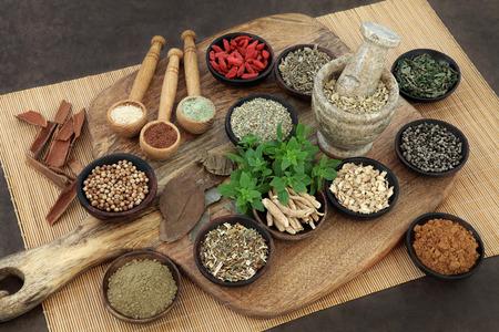 selezione di cibo erbe e spezie della salute per gli uomini in ciotole di legno e cucchiai. Utilizzato in erboristeria naturale alternativa. Archivio Fotografico