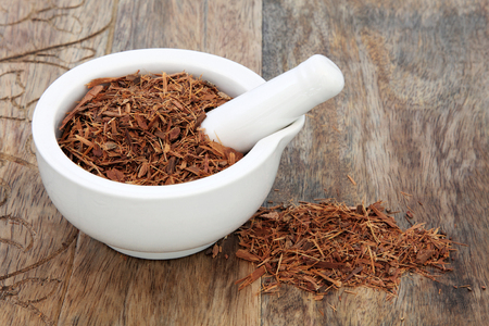 aphrodisiac: Catuaba bark herb used in natural alternative herbal medicine in a mortar with pestle over old wood background. Used as an aphrodisiac to increase libido. Stock Photo