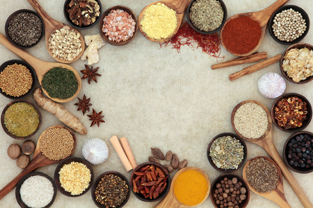 Herb and spice selection forming an abstract border over natural hemp paper background.