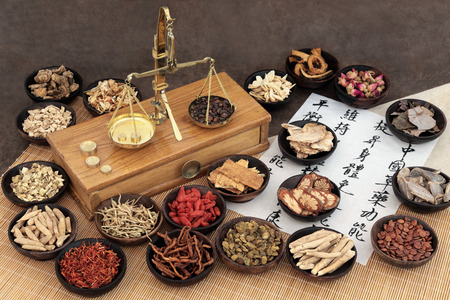 Chinese medicine ingredients with scales and calligraphy on rice paper. Translation read as chinese herbal medicine as increasing the bodys ability to maintain body and spirit health and balance energy. Stok Fotoğraf - 52585672