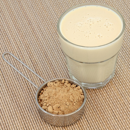 Maca root powder and drink in a glass over bamboo. Health and body building food. 스톡 콘텐츠