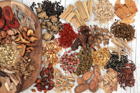 Traditional chinese herbal medicine ingredients on a maple wood board and loose over distressed white wood background. Stock Photo
