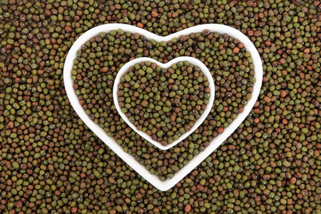 thiamine: Mung beans in heart shaped porcelain dishes forming an abstract background.