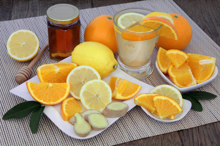 cold: Natural flu and cold remedy drink in a glass with orange and lemon fruit, fresh ginger and honey on bamboo  over oak background.