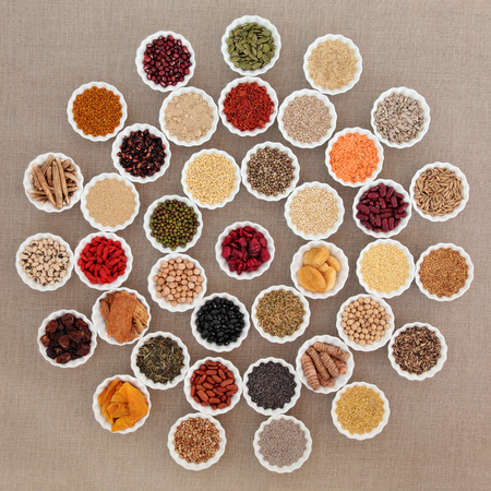 superfood: Large dried superfood selection in porcelain bowls in a circular design over hessian background.