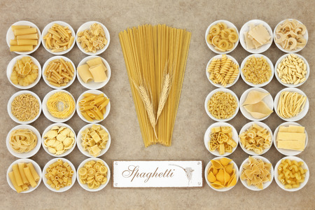 pasta: Dried pasta food varieties in round porcelain bowls with old spaghetti sign over natural hemp paper background