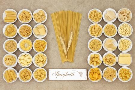 Variedades de alimentos secos en cuencos de porcelana de pasta redondas con viejos espaguetis firman sobre fondo de papel de cáñamo naturales