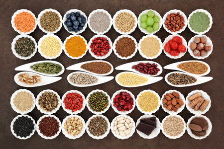 Health and diet superfood food selection in porcelain dishes over lokta paper background. High in vitamins, nutrients and antioxidants.