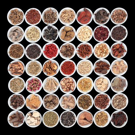 medicine background: Large traditional chinese herbal medicine collection in porcelain bowls over black background.