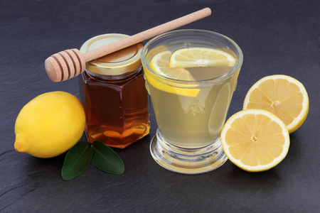 cold remedy: Honey and lemon drink for cold and flu remedy over slate background.