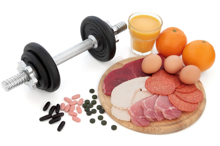 bacon and eggs: Body building dumbbell weights with supplement tablets, high protein food of chicken, steak, bacon, eggs, oranges and glass of smoothie juice over white background. Stock Photo