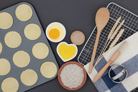 baking tray: Pastry dough shapes in baking tray with ingredients and utensils over grey background.