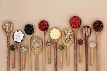 witaminy: Superfood for good health in wooden spoons forming an abstract background with copy space. High in antioxidants, vitamins and minerals.