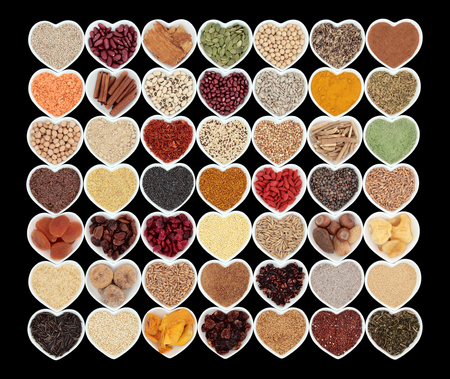super food: Large healthy dried super food in heart shaped bowls over black background. High in antioxidants, minerals and vitamins.
