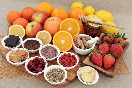 antioxidants: Large antioxidant food and herbal medicine selection for cold and flu remedy also high in vitamin c on an olive wood board over bamboo and hessian background.