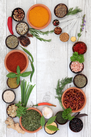 psyllium: Herb and spice selection in bowls with measuring spoons forming an abstract background border over distressed white wood. Stock Photo