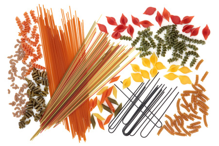 obtained: Dried coloured spaghetti pasta food selection forming an abstract background over white. Colouring obtained by using quid ink, spinach, tomato, carrot and beetroot vegetables. Stock Photo