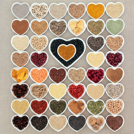 aphrodisiac: Large dried superfood collection in heart shaped porcelain bowls forming an abstract background over hessian background. High in minerals, vitamins and antioxidants.