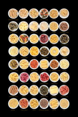 descriptive: Large dried pasta spaghetti collection in round porcelain bowls with descriptive titles for each variety over black background. Stock Photo
