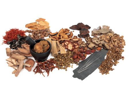 medicina tradicional china: Las agujas de acupuntura con hierbas chinas tradicionales en la medicina herbal sobre fondo blanco.