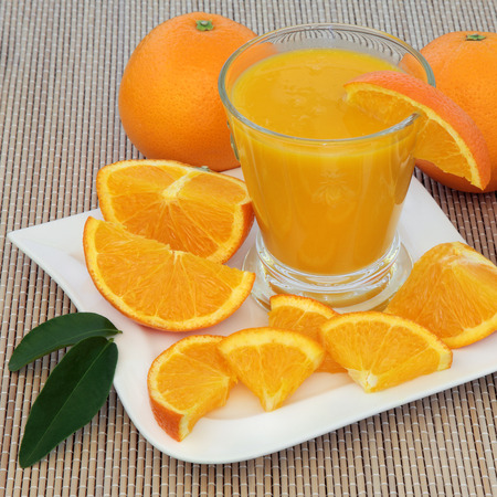 cold cure: Healthy fresh orange drink with oranges high in vitamin c and antioxidants over bamboo background. Stock Photo