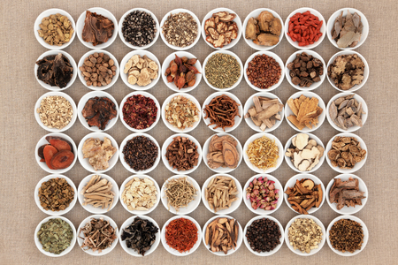 Chinese herbal medicine selection in white china bowls over hessian background. Stockfoto