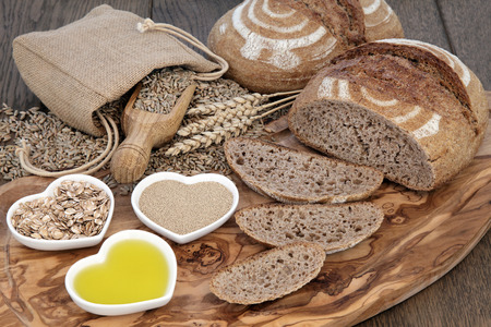 life loaf: Rustic still life of homemade brown bread sliced loaf, baking ingredients of yeast, oil, rye flakes and wheat in a hessian sack on olive wood board over oak background. Stock Photo