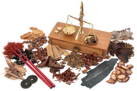 Traditionele Chinese acupunctuurnaalden met kruidenboter ingrediënten gebruikt in de kruidengeneeskunde met oude koperen schalen, i ching munten en eetstokjes op een witte achtergrond.