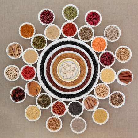 fiber food: Dried health food in china bowls forming an abstract wheel design over hessian background. Foods high in minerals, vitamins, antioxidants and dietary fiber.