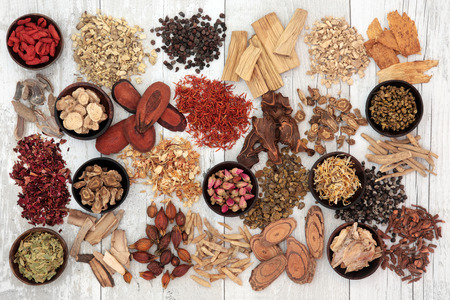 Traditional chinese medicine ingredients in wooden bowls and loose over distressed white wood background.