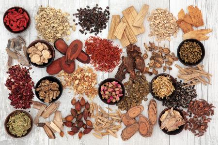 De traditionele Chinese geneeskunde ingrediënten in houten kommen en los over noodlijdende wit hout achtergrond. Stockfoto
