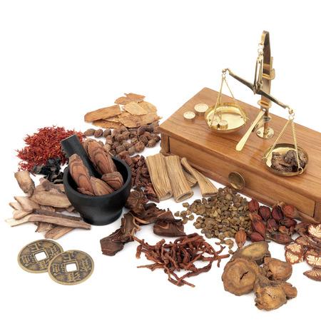 伝統的な中国のハーブ成分が白背景で古い真鍮スケールと代替漢方薬と乳棒と乳鉢で使用されます。 写真素材 - 53802006