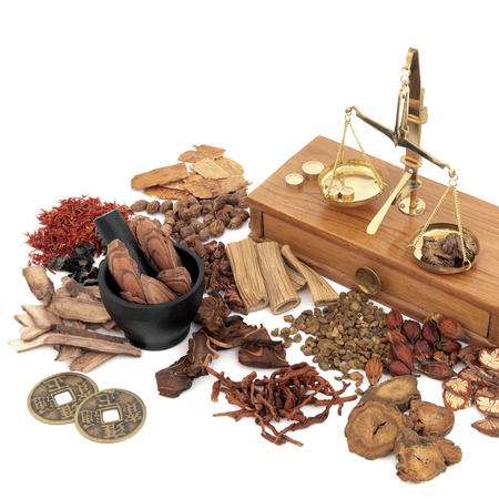 Traditional chinese herb ingredients used in alternative herbal medicine with old brass scales and mortar with pestle over white background.