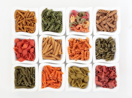 durum: Coloured italian pasta collection in china dishes over white background with spinach, carrot, tomato and durum wheat colouring.