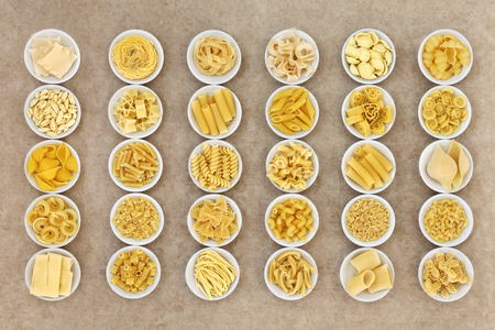 natural selection: Italian dried food pasta selection in round porcelain bowls over natural hemp paper background.