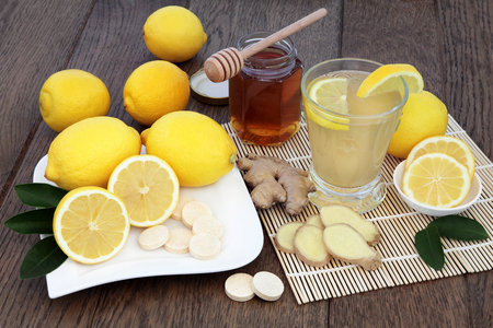 cold cure: Natural cold remedy drink with vitamin c tablets, with fresh ginger, lemon, honey and cinnamon spice over oak background.
