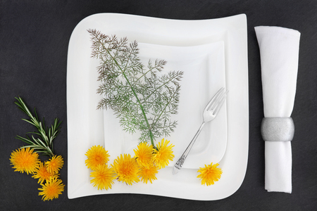 sliver: White porcelain table setting with two plates, antique sliver fork, linen napkin with dandelion flowers, rosemary and  bronze fennel herb over slate background.