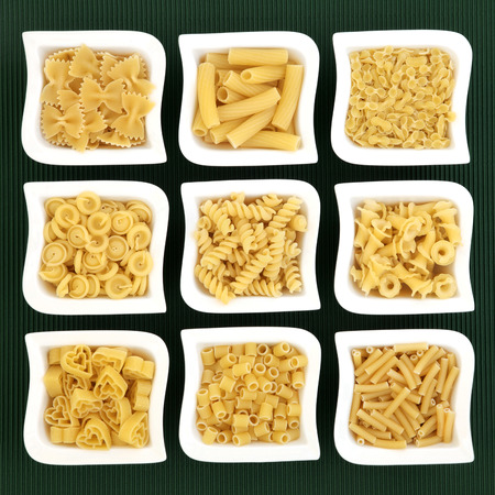 ridged: Italian dried food pasta selection in white porcelain dishes over ridged green background. Stock Photo